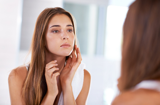 Concerned woman looking in the mirror and touching her face